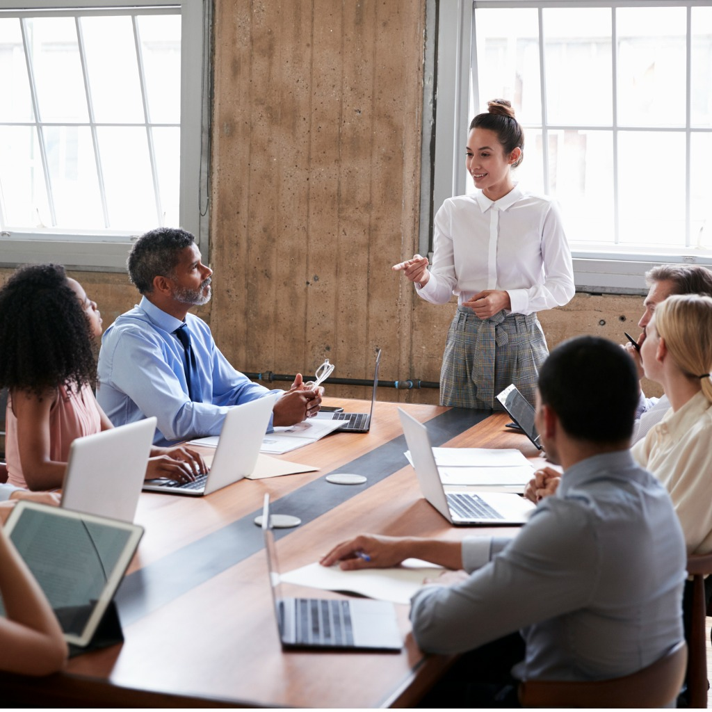 female-manager-stands-addressing-team-at-board-meeting-picture-id904596172